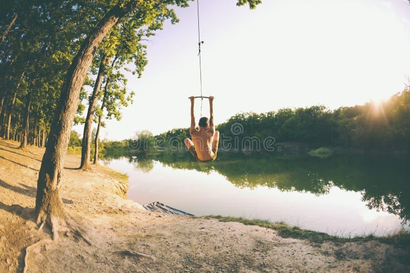 Salte en el agua Un hombre está descansando sobre el lago Un oscilación de una cuerda y de un palillo Reconstrucción activa en na fotos de archivo