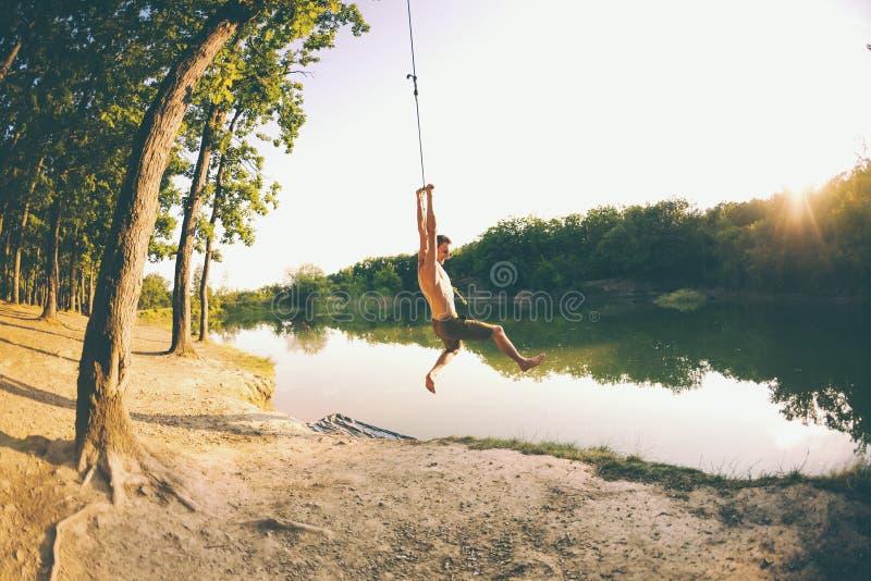 Salte en el agua Un hombre está descansando sobre el lago Un oscilación de una cuerda y de un palillo Reconstrucción activa en na imagenes de archivo