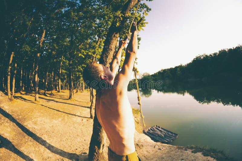 Salte en el agua Un hombre está descansando sobre el lago Un oscilación de una cuerda y de un palillo Reconstrucción activa en na fotografía de archivo libre de regalías