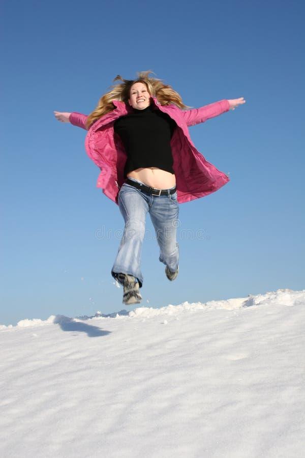Salte a la muchacha del invierno foto de archivo