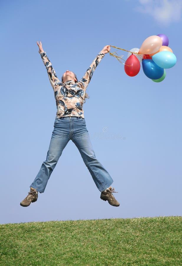 Salte a menina com balões fotografia de stock