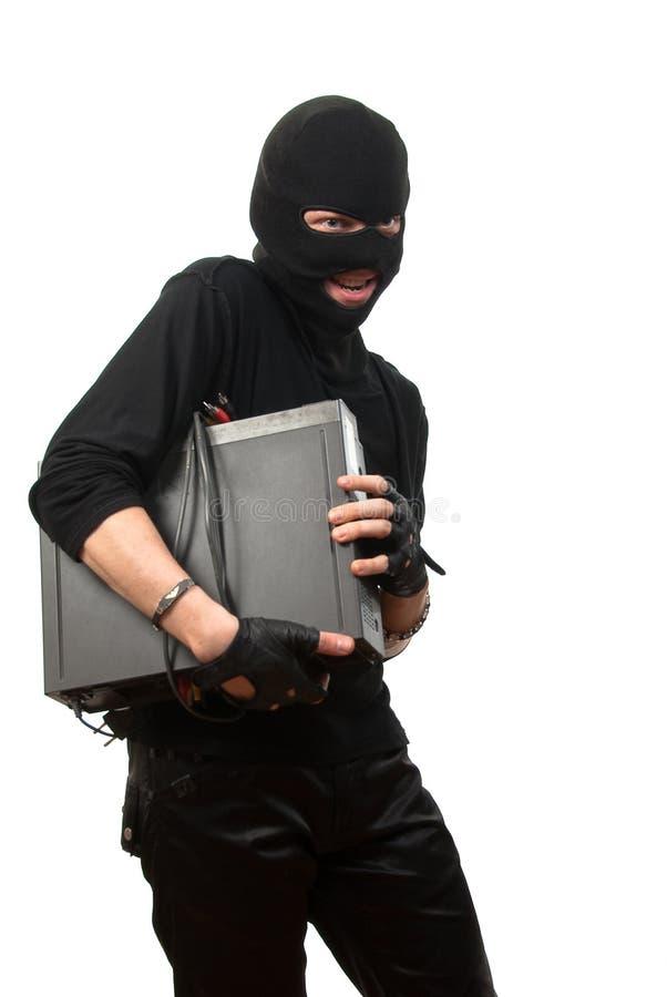 Salteador em uma máscara com dispositivo nas mãos foto de stock