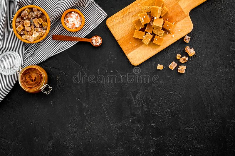 Salted caramel background. Melted caramel in glass jar, caramel cubes on cutting board, sugar and salt on black desk top. View royalty free stock photo