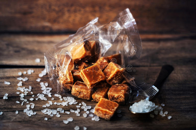 Salted caramel pieces and sea salt close up. Butter caramel can royalty free stock image