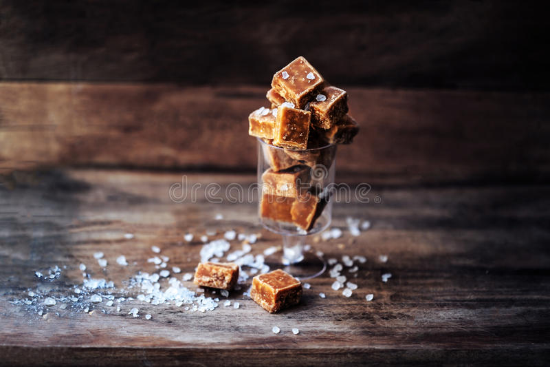 Salted caramel pieces and sea salt macro. Butter caramel candy m royalty free stock photo