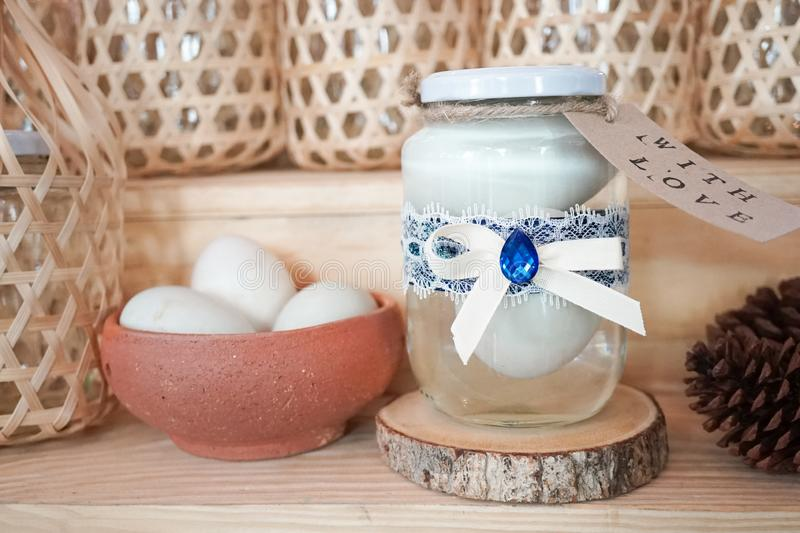 Salted eggs in a glass jar, with blue ribbon and lace DIY gift wrapping. Ideas for New Year present using eggs. stock image