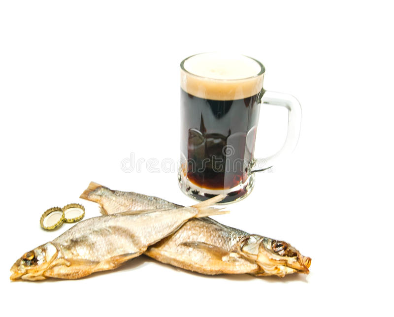 Salted fish and glass of dark beer on white royalty free stock photography