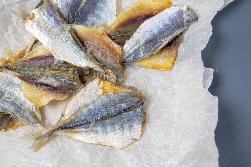 Salted fish lies in unfolded paper royalty free stock photo