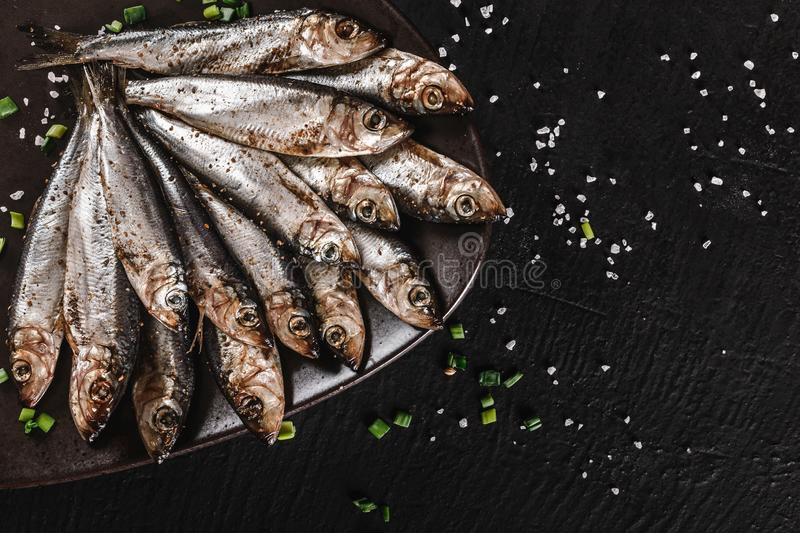 Salted fishes sprat marinated with spices, salt on plate over dark stone background. Mediterranean food, appetizer, seafood, top royalty free stock image