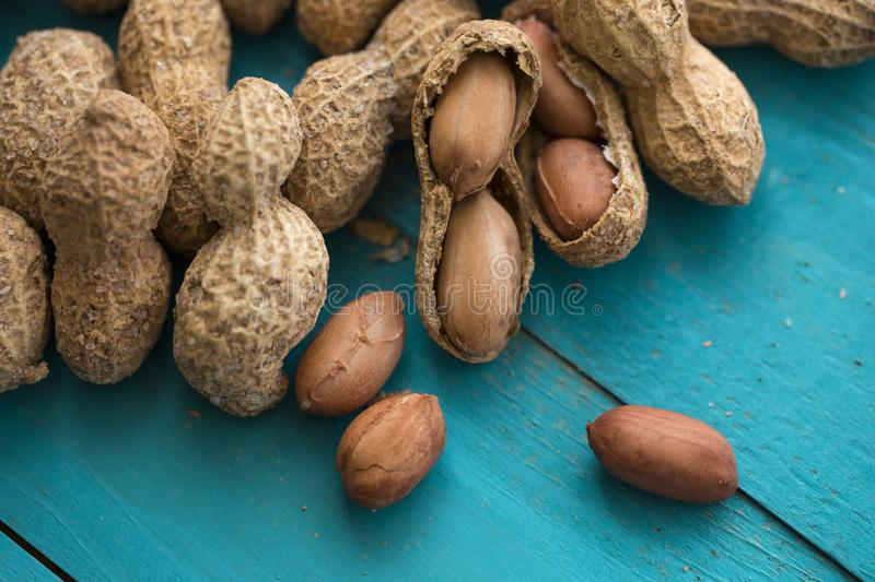 Salted peanuts or groundnut. Salted and shelled peanuts or groundnut on turquoise background stock photo
