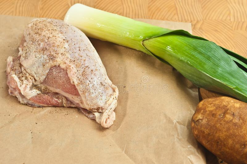 Salted and peppered raw, organic, chicken breast, washed leek, and potato, on a bamboo wood cutting board,. Top view, close medium distance, of a salted and royalty free stock photos