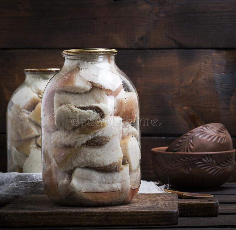 Salted pieces of lard with meat are closed in glass jars royalty free stock images