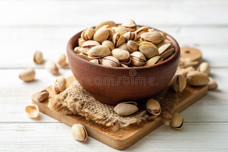 Salted pistachio nuts in ceramic bowl on white wooden background. Selective focus royalty free stock photography