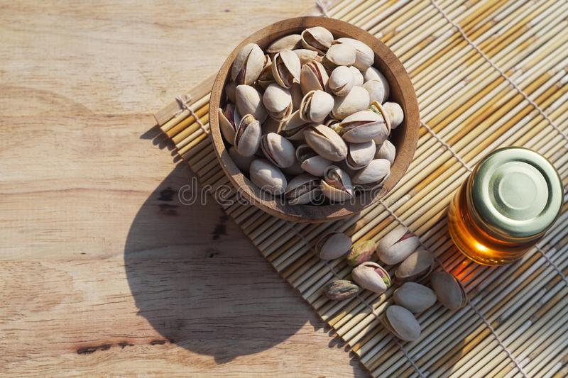 Salted pistachio in wooden bowl on wood table with green banana leaf background, copy space royalty free stock photos