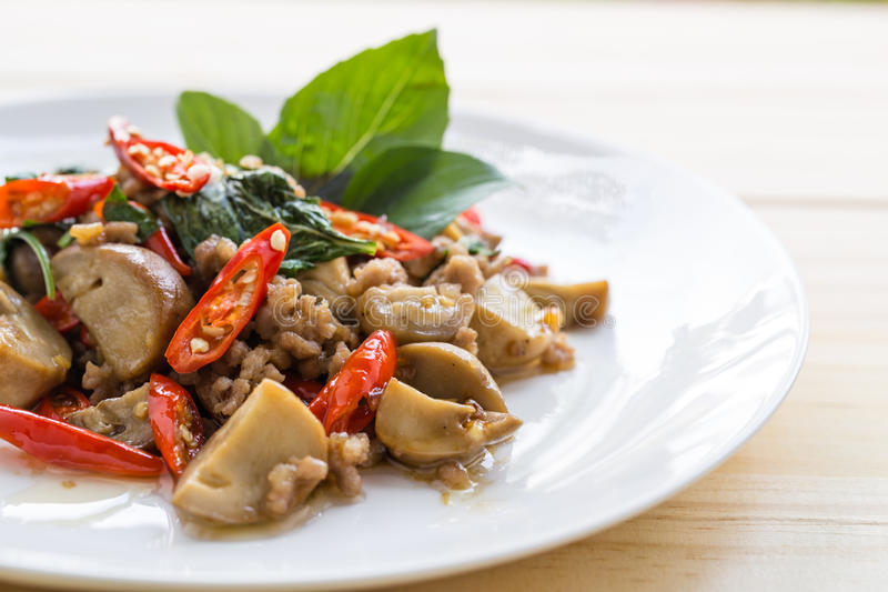 Salted pork with chili & Basil leaves in plate on table. stock image