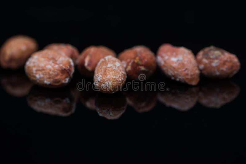 Salted a rôti des arachides étroites vers le haut du macro tir sur la surface noire brillante photo libre de droits