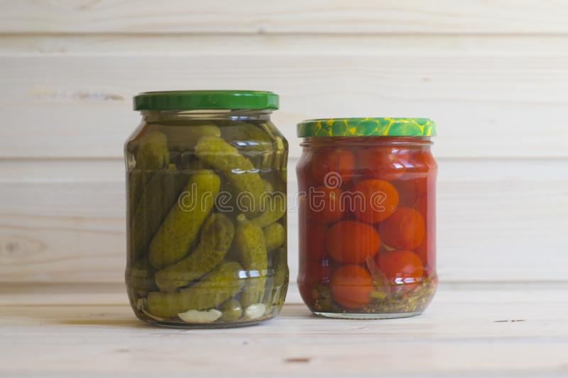 Salted red tomatoes and green gherkins in jars on a light wooden royalty free stock photos