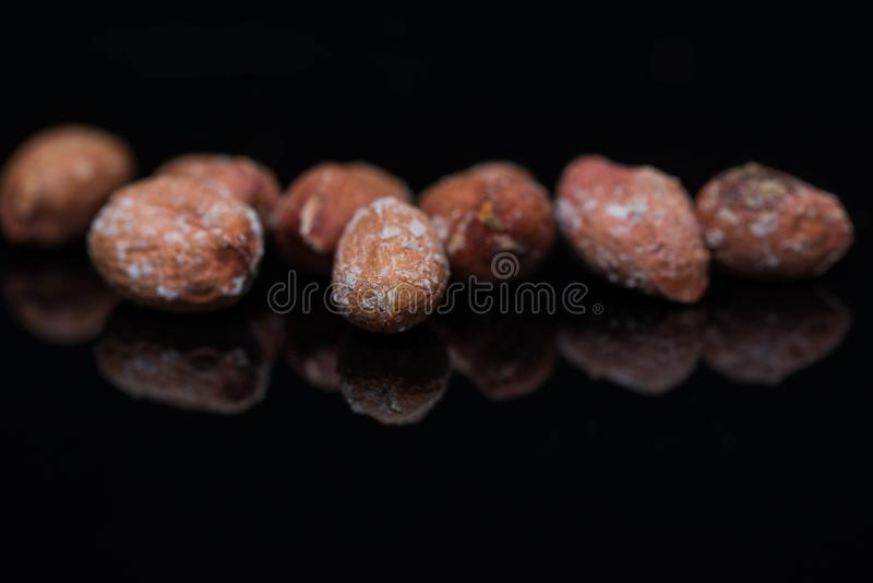 Salted roasted peanuts close up macro shot on shiny black surface royalty free stock photo