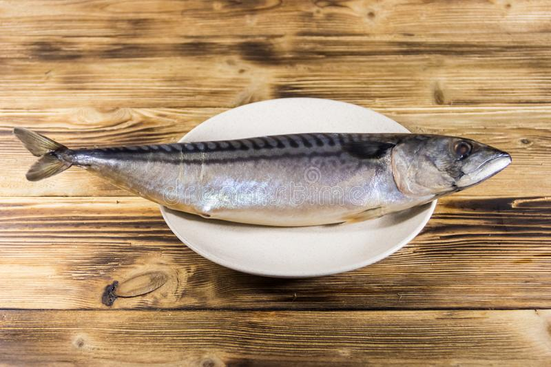 Salted scomber fish on a plate. Whole mackerel on wooden table royalty free stock photo