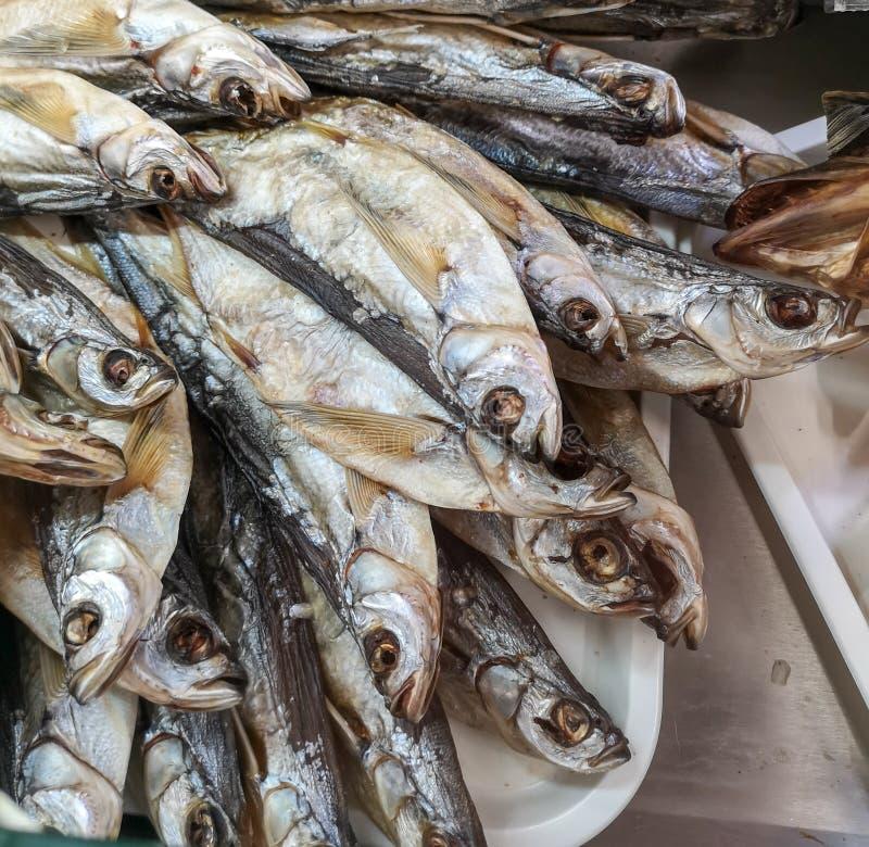Salted secó pescados en el estante del mercado foto de archivo