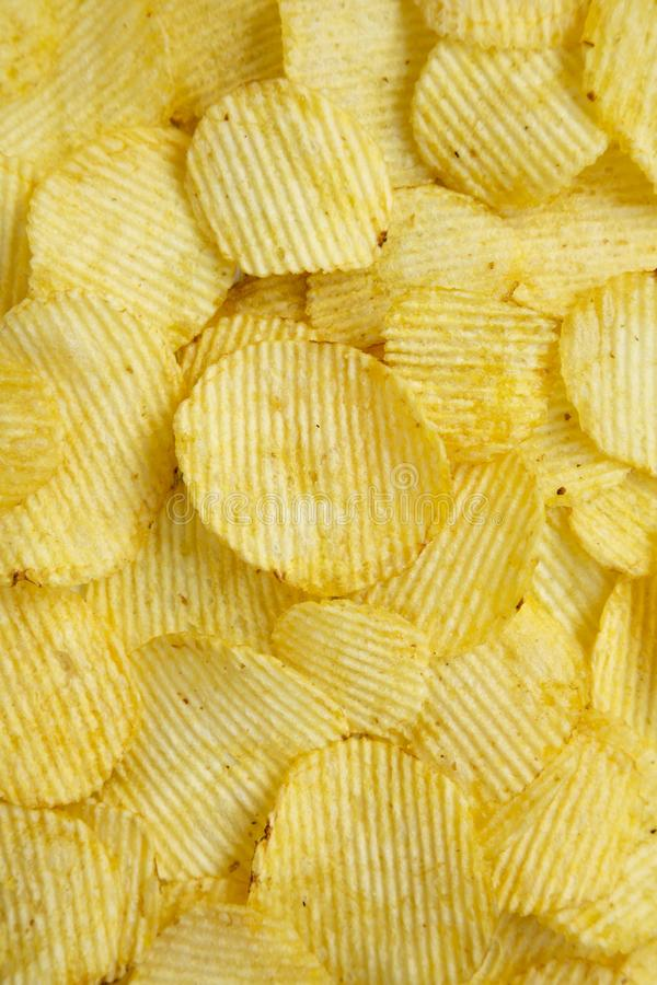 Salted wavy potato chips, top view. Overhead, from above, flat lay. Close-up.  royalty free stock image