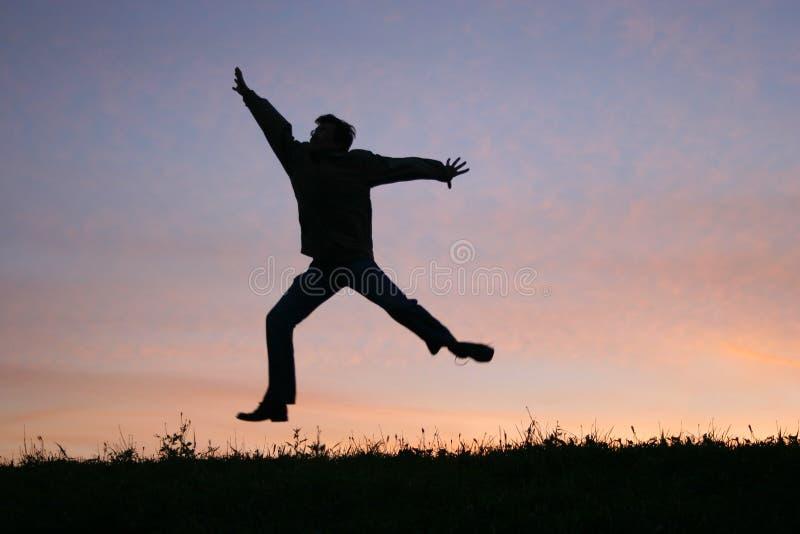 Salti l'uomo sul tramonto fotografia stock libera da diritti