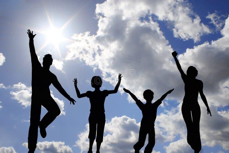 Salti la famiglia di quattro sul cielo fotografia stock libera da diritti
