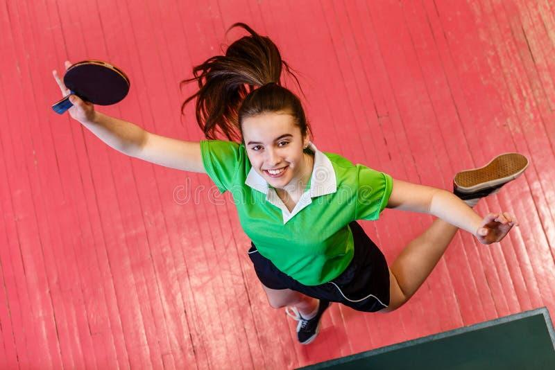 Salto adolescente sonriente alegre de la muchacha Muchacha adolescente que sostiene una estafa de tenis de mesa fotografía de archivo libre de regalías
