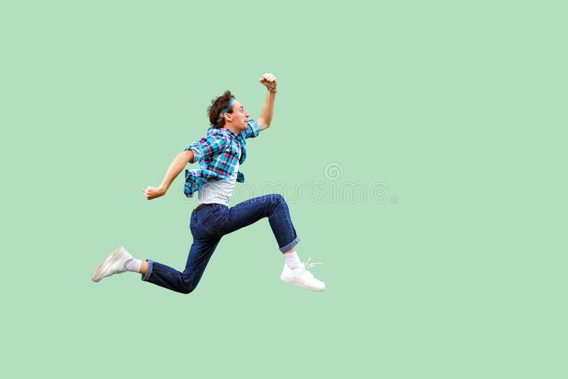 Salto al éxito Vista lateral del perfil integral del hombre joven activo en camisa a cuadros azul casual y la venda que corren mu fotos de archivo