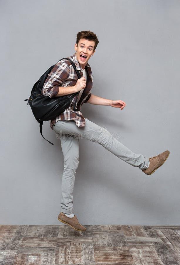 Salto alegre engraçado do estudante masculino foto de stock
