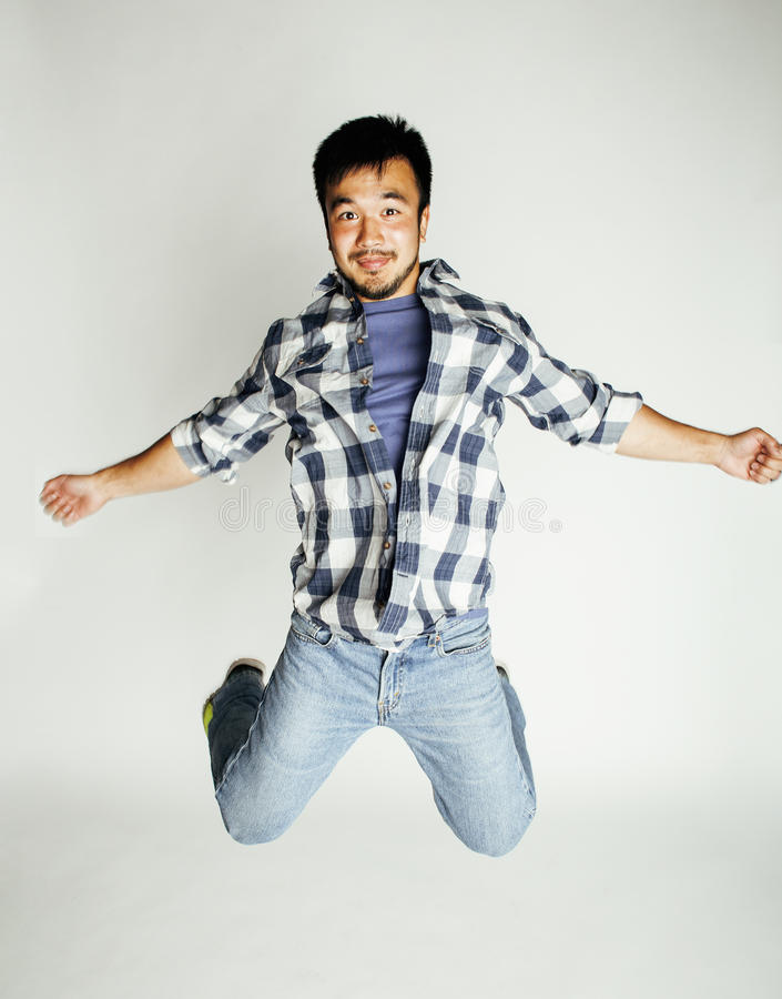 Salto asiático bonito novo do homem alegre contra o fundo branco, conceito dos povos do estilo de vida foto de stock royalty free