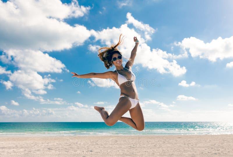 Salto asiático da mulher do biquini feliz da alegria na praia Vacat tropical imagens de stock