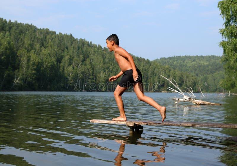 Salto asiático feliz del muchacho en el lago imagen de archivo libre de regalías
