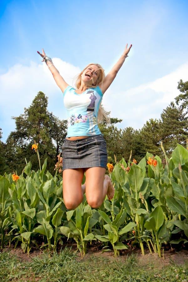 Salto blondy feliz hermoso imagen de archivo libre de regalías