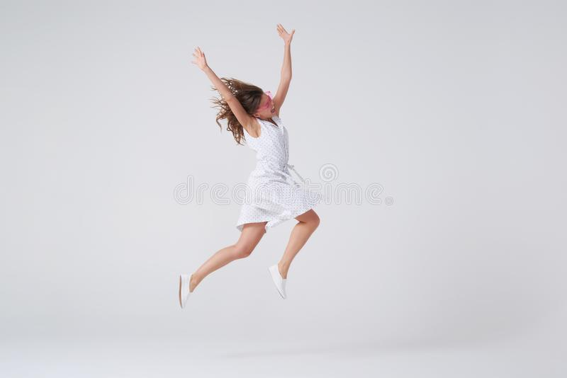 Salto bonito alegre da jovem mulher fotografia de stock royalty free