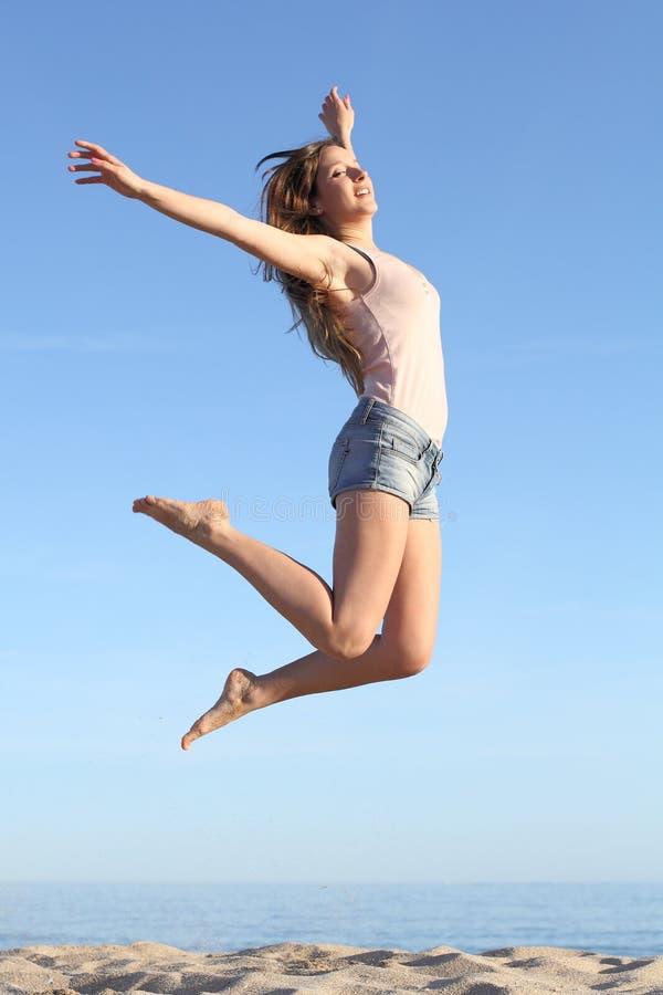 Salto bonito da mulher feliz na praia fotos de stock royalty free