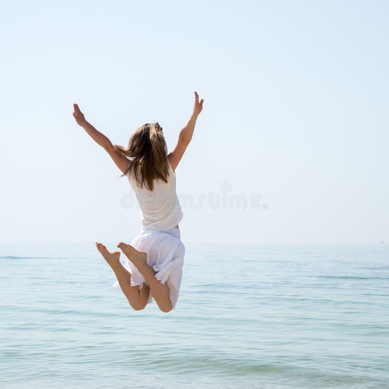Salto bonito feliz da moça fotografia de stock