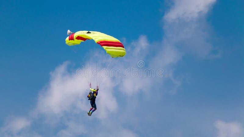 Salto com um paraquedas colorido em tandem em um céu azul com nuvens, adrenalina e risco brancos imagens de stock