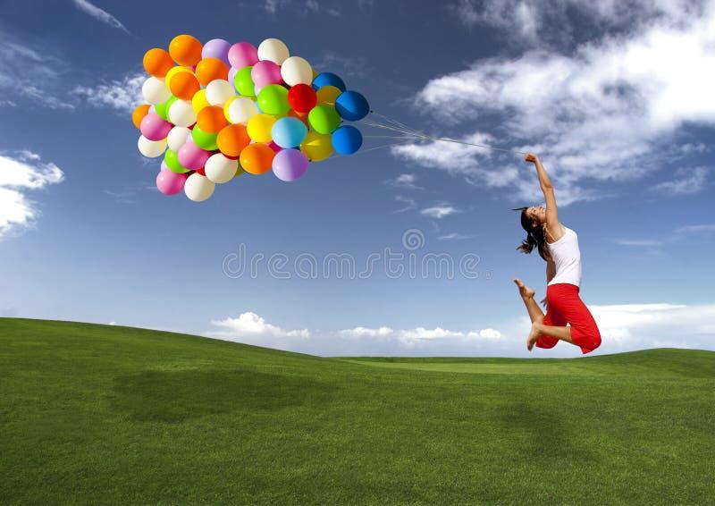 Salto con los globos foto de archivo