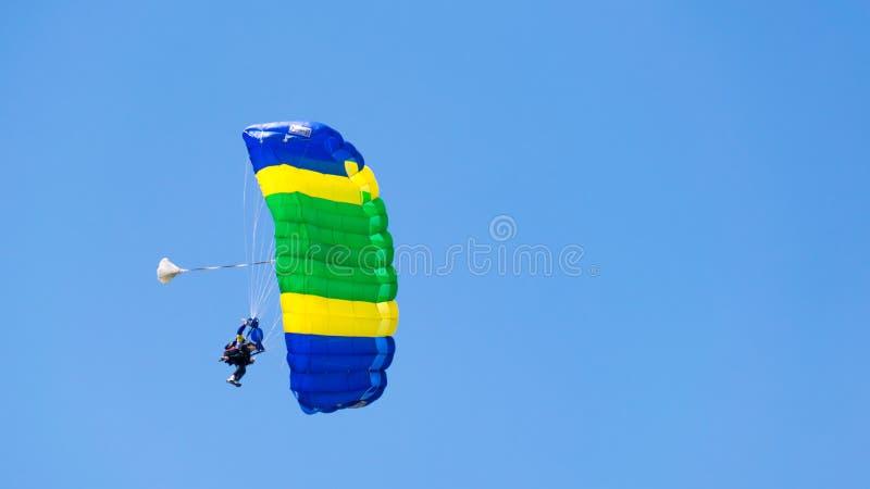 Salto con un paracaídas coloreado en tándem en un cielo azul con las nubes, la adrenalina y el riesgo blancos fotografía de archivo libre de regalías