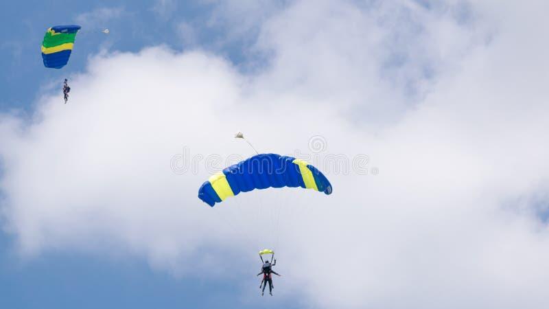 Salto con un paracadute colorato in tandem su un cielo blu con le nuvole, l'adrenalina ed il rischio bianchi immagine stock