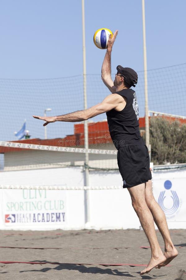 Salto da bola do serviço do jogador de voleibol da praia do homem imagens de stock