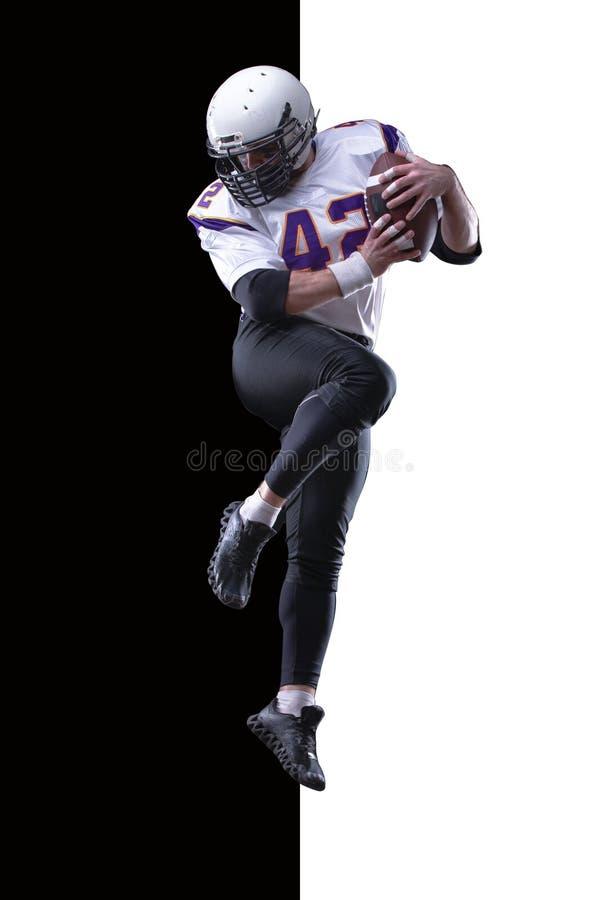Salto de altura del futbolista americano fotos de archivo