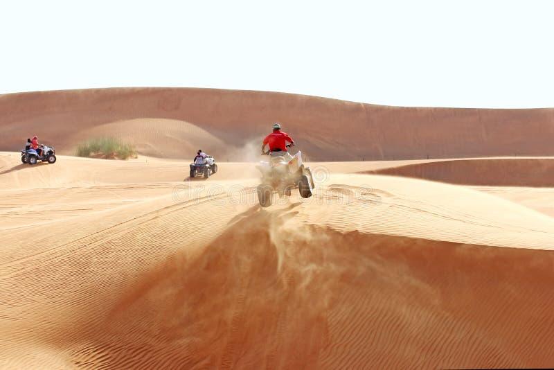 Salto de ATV en una duna de arena imagen de archivo