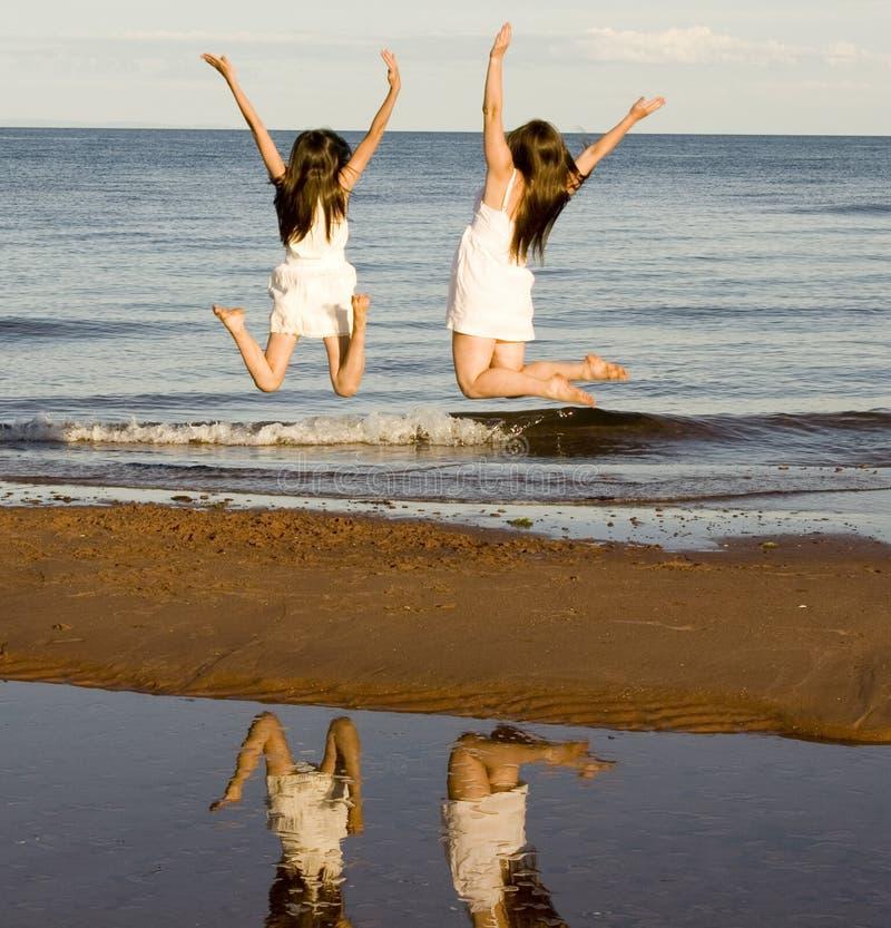 Salto de dos muchachas fotos de archivo