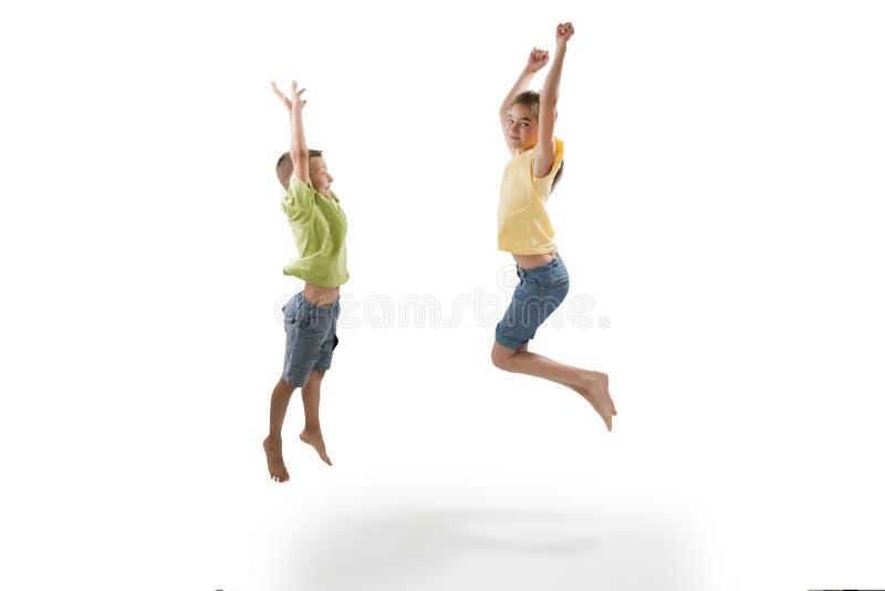 Salto de dos niños imagenes de archivo