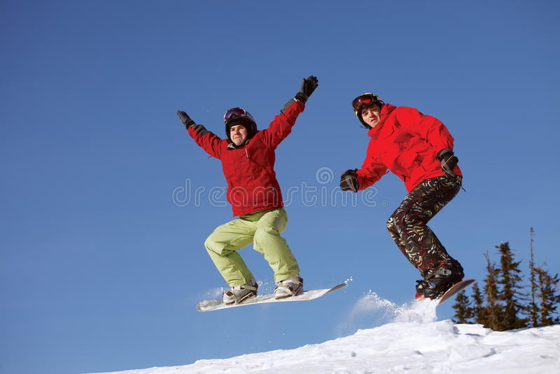 Salto de dos snowboarder imagen de archivo