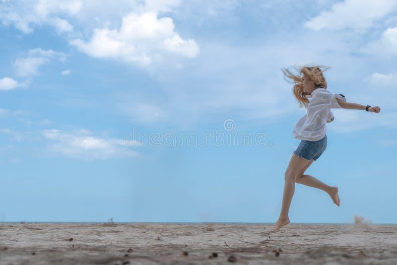 Salto de fatura fêmea no Sandy Beach com céu azul fotografia de stock royalty free