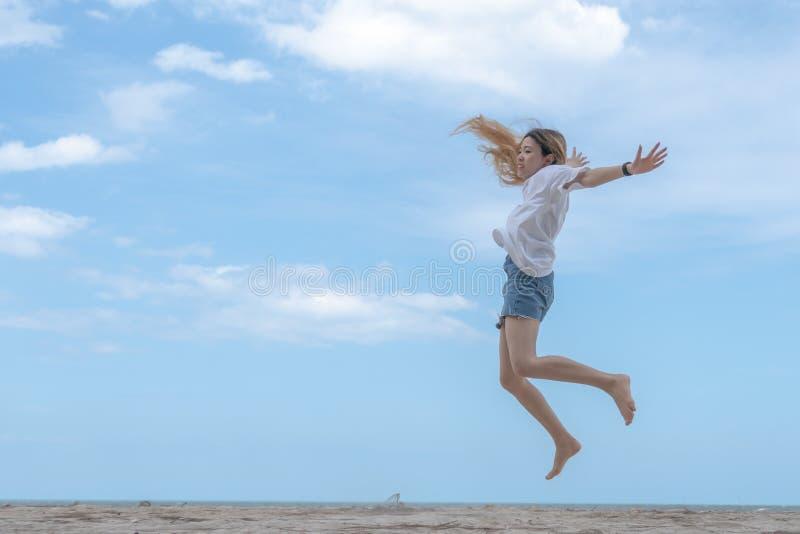 Salto de fatura fêmea no Sandy Beach com céu azul fotos de stock
