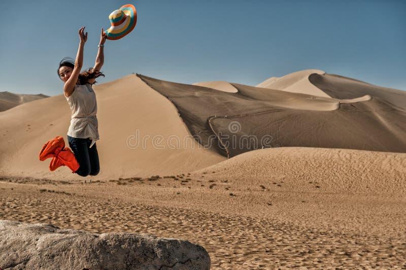 Salto de la alegría en las dunas de arena de Mingsha imagenes de archivo